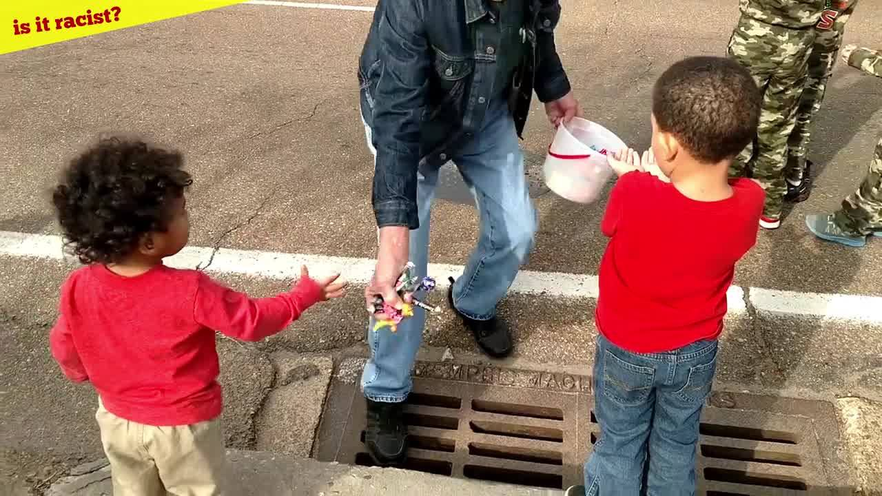White man tosses candy on the ground for black kids